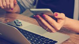 Женщина сидит за ноутбуком со смартфоном в руке