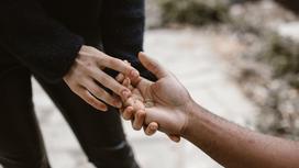 Девушка кладет в руку парня обручальное кольцо