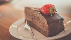 Кусочек шоколадного торта, украшенного клубничкой, на тарелке