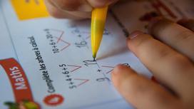 ребенок пишет ручкой в тетрадке