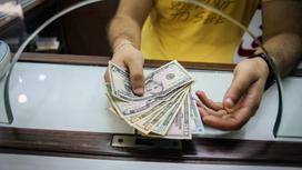 Мужчина протягивает кассиру доллары