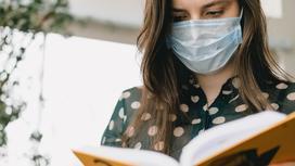 Девушка в маске читает книгу