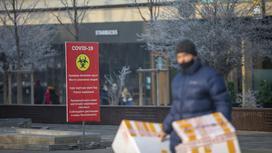 Мужчина идет по улице на фоне баннера с информацией по COVID-19