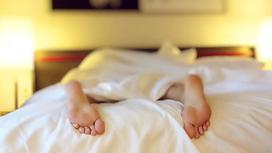 Человек в кровати, стопы крупным планом