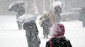 Люди идут с зонтами по улице во время сильного снегопада