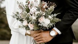 Жених и невеста держат в руках свадебный букет