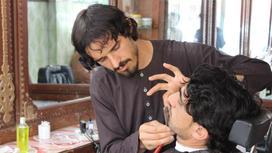 Парикмахер из Афганистана с клиентом