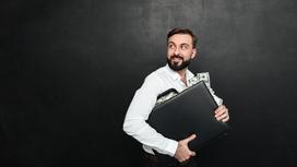Мужчина держит кейс с деньгами