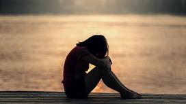 Девочка сидит на мосту, обняв колени