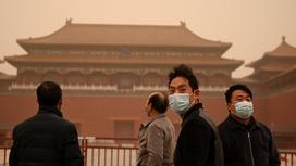 Люди во время песчаной бури в Пекине