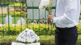 мужчина с цветами стоит на кладбище