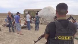 Боец СОБР в бронежилете с автоматом на фоне группы мужчин