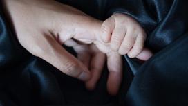 маленький ребенок держит маму за руку