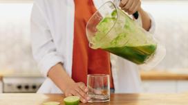 Женщина наливает смузи в стакан