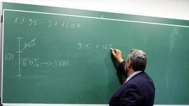Преподаватель чертит мелом на доске