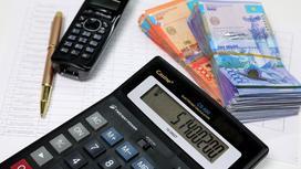Калькулятор, деньги, телефон и ручка лежат на листах бумаги