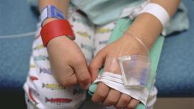 Ребенок в пижаме с катетером на руке