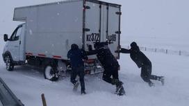 Трое мужчин толкают грузовик по дороге