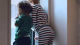 Двое детей смотрят в окно