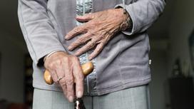 Пожилая женщина держит трость