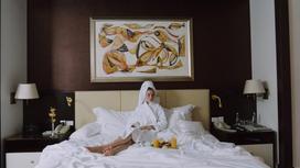Девушка лежит на кровати в номере отеля