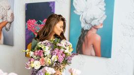 Девушка с букетом цветов на фоне висящей на стене современной живописи