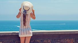 Девушка в шляпке смотри на море