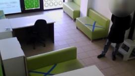 Мужчина в черном пальто стоит в холле помещения