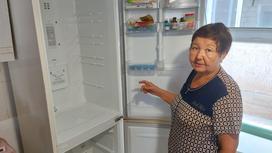 Женщина показывает холодильник
