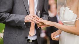 Мужчина надевает кольцо на палец невесте