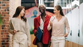 Три девушки улыбаются и разговаривают на ходу