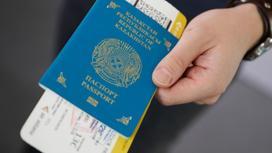 Человек держит казахстанский паспорт