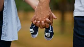 Две руки держат детскую обувь