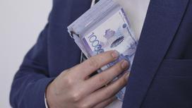мужчина кладет пачку денег в карман пиджака