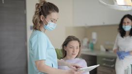 Врач в маске стоит возле пациентки