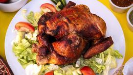 Запеченная курица на тарелке с овощами