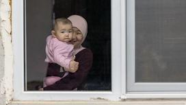 Женщина с ребенком стоит у окна