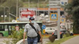 Мужчина в маске идет по городу