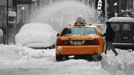 Такси стоит в заснеженном переулке