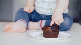 Ребенок трогает пальцем шоколадный кекс