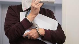 Женщина в наручниках прикрывает лицо газетой