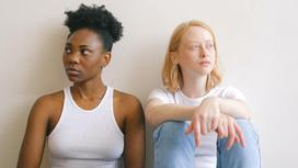 Девушки сидят у стены после ссоры