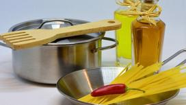 Кастрюля, деревянная лопатка, спагетти в миске, красный острый перец, масло в бутылках