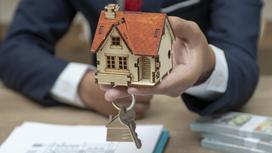 Мужчина держит в руках модель дома