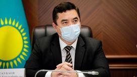 Нурлан Таубаев в маске сидит за столом