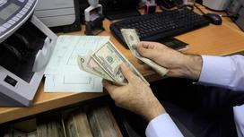 Мужчина считает доллары за столом
