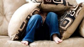 Ребенок сидит на диване