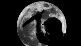 мужчина с занесенным в руке ножом на фоне Луны