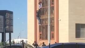 Мужчина свисает из окна