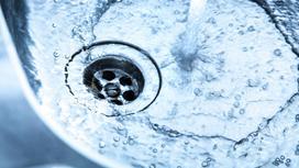 Вода из крана течет в сливное отверстие раковины